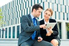Trabajo de los empresarios al aire libre con la tableta Foto de archivo