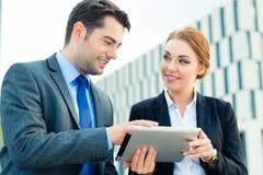 Trabajo de los empresarios al aire libre con la tableta Foto de archivo libre de regalías