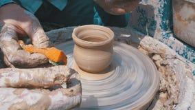Trabajo de manos del ` s del alfarero con la arcilla en una rueda del ` s del alfarero almacen de video