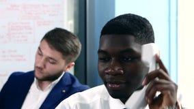 Trabajo de oficina, afroamericano que habla en el teléfono metrajes