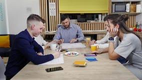Trabajo de oficina por la ma?ana Los colegas trabajan en el t? de la tabla y de la bebida, almacen de metraje de vídeo