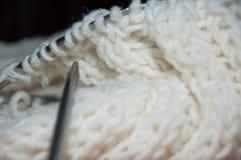 Trabajo de punto Bufanda blanca de las lanas y aguja que hace punto Foto de archivo