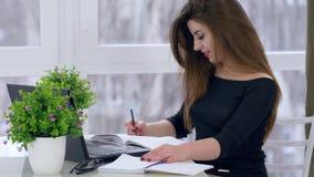 Trabajo de secretaria, hembra del negocio que hace notas en el cuaderno que se sienta en la tabla en sitio almacen de metraje de vídeo