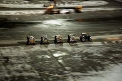 Trabajo de servicios técnicos en el aeropuerto El tractor es rápidamente afortunado varios carros con la carga llena Fotos de archivo