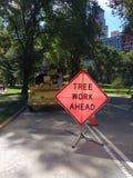Trabajo del árbol a continuación que advierte la señal de tráfico, Central Park, New York City fotografía de archivo libre de regalías