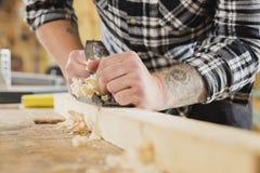 Trabajo del carpintero con el avión en el tablón de madera fotos de archivo libres de regalías
