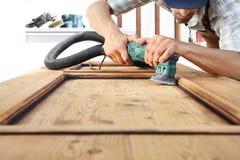 Trabajo del carpintero la madera con la chorreadora fotos de archivo