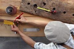 Trabajo del carpintero la madera, midiendo con el cartabón y el lápiz viejos imágenes de archivo libres de regalías