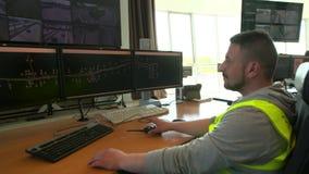 Trabajo del despachador del servicio del camino con el ordenador dentro de la sala de control moderna almacen de video