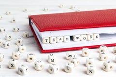 Trabajo del equipo de la frase escrito en bloques de madera en cuaderno rojo en whi Imagen de archivo libre de regalías