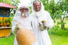 Trabajo del equipo del apicultor al aire libre con el fumador Fotografía de archivo