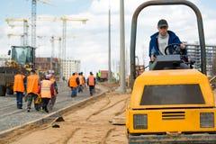 Trabajo del equipo durante la construcción de carreteras Imagenes de archivo
