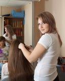 Trabajo del estilista de pelo sobre el pelo de la mujer Fotos de archivo