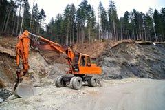 Trabajo del excavador sobre el camino Fotografía de archivo