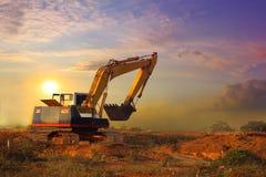 Trabajo del excavador y tierra móvil por tarde de la construcción Fotos de archivo libres de regalías