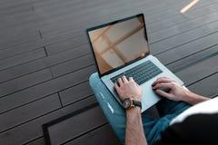 Trabajo del freelancer del hombre joven Las manos de los hombres y un ordenador portátil moderno del metal Hora laborable Visión  fotos de archivo libres de regalías