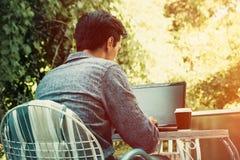 Trabajo del hombre joven en línea sobre el ordenador portátil al aire libre foto de archivo