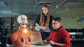 Trabajo del hombre y de la mujer con el robot biónico en un cuarto, cierre para arriba metrajes