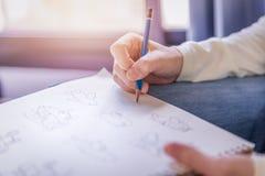 Trabajo del lápiz del dibujo de la mano de la mujer sobre el Libro Blanco Imagenes de archivo