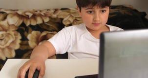 Trabajo del niño con el ratón de la PC cerca del ordenador portátil en la tabla blanca almacen de video
