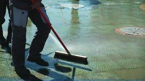 Trabajo del portero, limpieza de calles Calles de limpieza de la ciudad con la manguera del agua Asfalto de limpieza del barrende almacen de metraje de vídeo