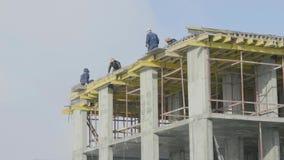 Trabajo del sitio de la construcción de edificios contra el cielo azul Trabajadores en el emplazamiento de la obra de una constru almacen de metraje de vídeo