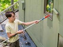 Trabajo del verano del adolescente que pinta la casa Imagenes de archivo