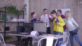 Trabajo diario en la oficina, empleados que se dan altos cinco y conseguir trabajar sentarse en la tabla con el ordenador y los o metrajes