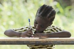 Trabajo difícilmente en la escuela - niño africano que aprende y escritura Imagen de archivo