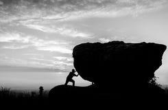 Trabajo duro La persona rueda la roca en la montaña Foto de archivo