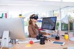 Trabajo ejecutivo femenino en el ordenador portátil mientras que usa las auriculares de la realidad virtual Imagen de archivo libre de regalías