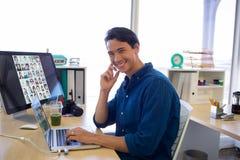 Trabajo ejecutivo masculino sobre el ordenador portátil en su escritorio Foto de archivo