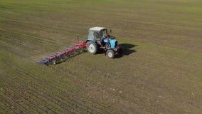 Trabajo en el terreno en la primavera El tractor harrows la tierra, vista lateral, encuesta aérea almacen de video