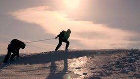 trabajo en equipo bien-coordinado en turismo del invierno los escaladores implicaron con una colina nevosa de la subida de la cue almacen de metraje de vídeo