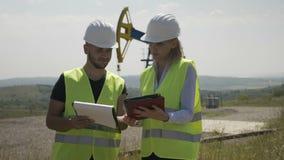 Trabajo en equipo de los ingenieros en industria del campo petrolífero que analizan proyecto de la ingeniería sobre la tableta ce almacen de video