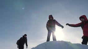 Trabajo en equipo de los turistas, subiendo la montaña, ayudándose, alcanzando el top Superar dificultades, mano amiga almacen de video