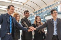 Trabajo en equipo del negocio de cinco asiáticos con un grupo de personas con las manos t Foto de archivo