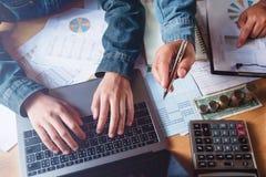 trabajo en equipo del negocio que comprueba informe de la contabilidad en oficina con usin imagen de archivo