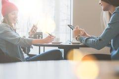 Trabajo en equipo, dos empresarias jovenes que se sientan en la tabla en café y que trabajan en smartphones La primera muchacha e imagen de archivo