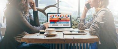 Trabajo en equipo, dos empresarias jovenes que se sientan a través de la tabla de uno a En el ordenador portátil de la tabla, la  imagen de archivo libre de regalías