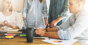 Trabajo en equipo, intercambio de ideas El grupo de empresarios jovenes trabaja junto en oficina en la tabla, leyendo los documen fotografía de archivo