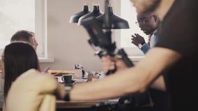 Trabajo en equipo multiétnico de los colegas en oficina sana moderna El hombre afroamericano se sienta en la tabla, juegos con po almacen de video