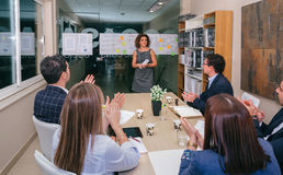 Trabajo en equipo que aplaude al jefe de la mujer para el éxito en proyecto del negocio Foto de archivo
