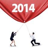 Trabajo en equipo que tira de la bandera del Año Nuevo de 2014 Foto de archivo libre de regalías