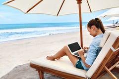 Trabajo en la playa Mujer de negocios que trabaja en línea en el ordenador portátil al aire libre Foto de archivo libre de regalías