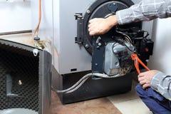 Trabajo en una hornilla de calefacción dañada Foto de archivo