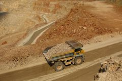Trabajo enorme de los camiones en una explotación minera de la mina Foto de archivo libre de regalías