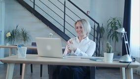 Trabajo feliz del acabamiento de la mujer de negocios en oficina metrajes