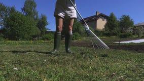Trabajo femenino con el rastrillo en prado