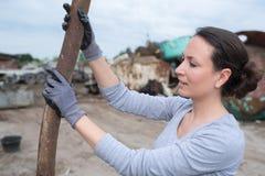Trabajo femenino con las barras de metal viejas en el scrapyard Fotos de archivo